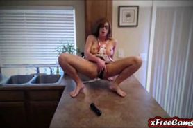 Hot busty MILF masturbates in kitchen