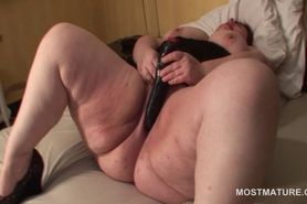 Big tits mature fucks herself with a dildo