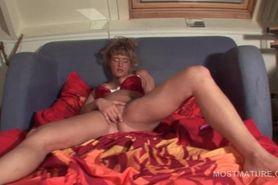 Mature blonde in lingerie pleasing herself