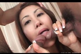 Playful jap babe eating two loaded peckers at once